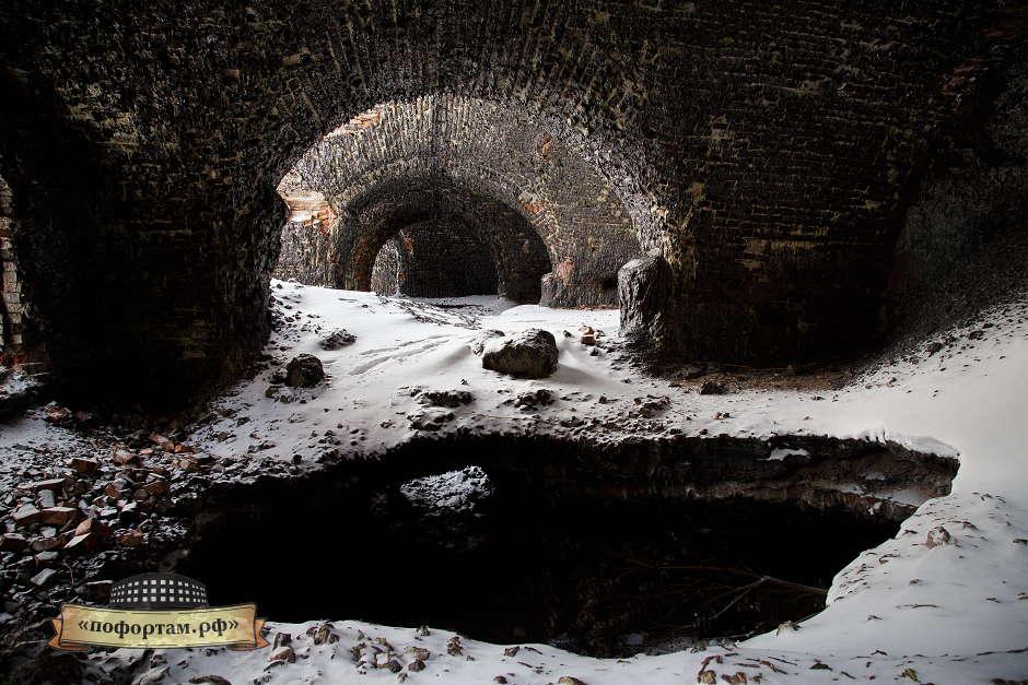 От свежего снега отражается свет, освещая своды казематов