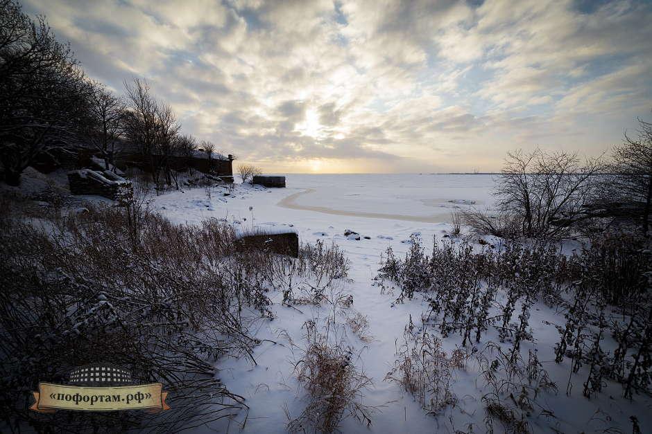 Гавань форта защищена от восточных волн ряжами - древесно-землянные укрепления установленные на дне. На мой взгляд, больше напоминает лагуну Летом это место очень живописное - песчаный пляж. За спиной обилие растительности. У берега затоплено несколько тральщиков. Рубка одного видна над поверхностью воды.